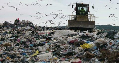 Bulldozer flattening garbage in a landfill waste site