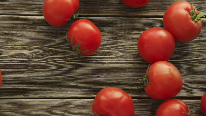 Tomatoes roll over the screen in slow motion on wooden background. HD
