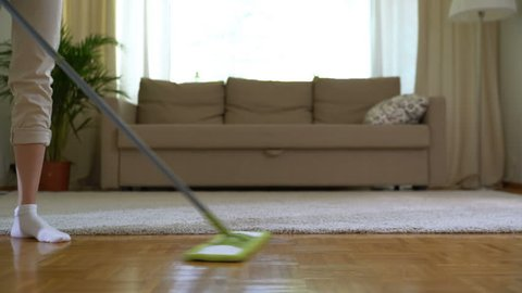 Woman cleaning parquet floors in the living room. Close-up.