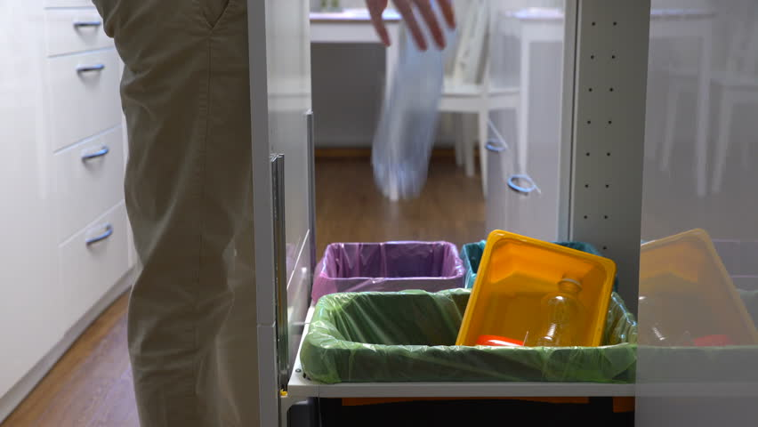 Young woman drops the trash into kitchen recycling bin.