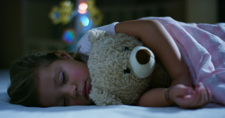 baby rests quietly in bed hugging a teddy bear toy, concept of peaceful dreams and homes without noise, happy children and mom and dad happy. happiness in sleep, children without coughing.