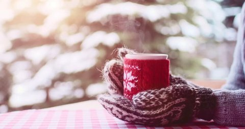 Hands in Knitted Mittens holding Steaming Cup of Hot Coffee or Tea on Snowy Winter Morning Outdoors. 4K DCi SLOW MOTION 120 fps.