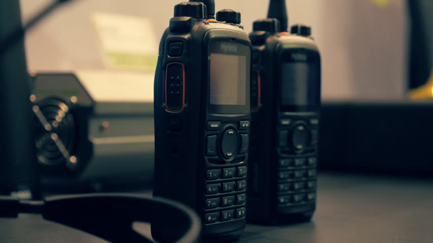 Two walkie-talkie on the table. Dolly shot. Shallow depth of field