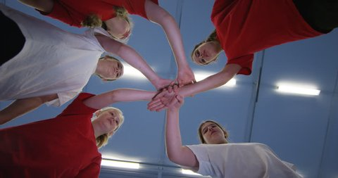 4K Low angle view looking up, young girls standing in a circle in school gym put hands together before sports game