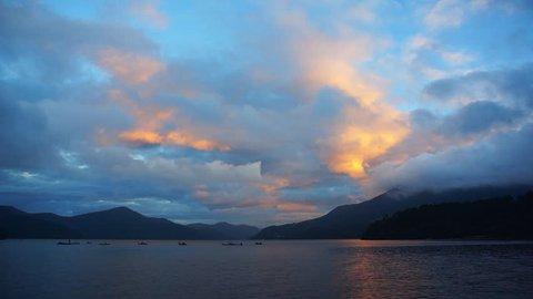 Mountain lake, caldera sunrise, sunset with fishing boats in the distance. Lake Ashi, Hakone, Japan