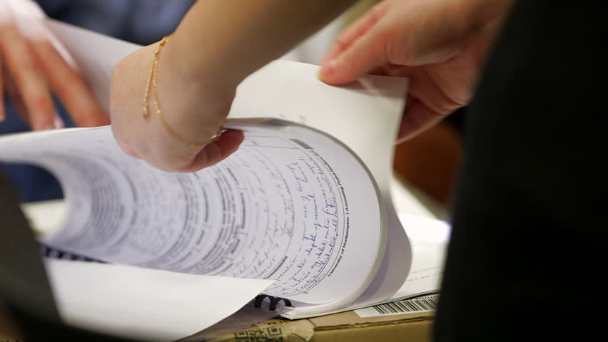 Woman turns page of hand written doument