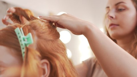 Female hairdresser making hairstyle to foxy girl in beauty salon Slow motion