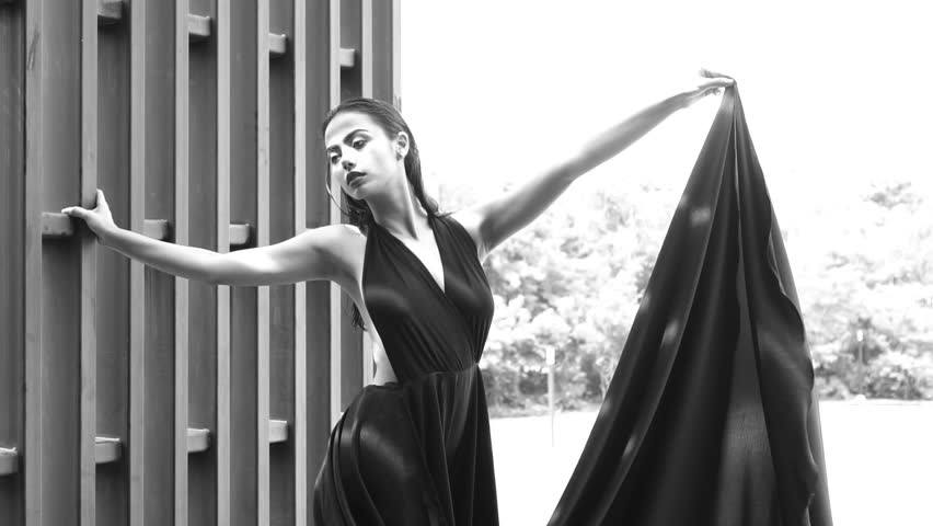 Gorgeous fashion woman with dark hair in elegant black dress posing leaning against modern wall in tropical garden - black and white video in slow motion #20758975