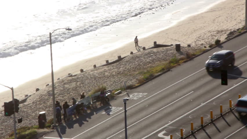 A long shot of the Pacific Coast Highway, with many people waiting at a bus stop.