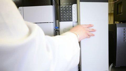 Scientist opens liquid chromatograph mass spectrometer cover