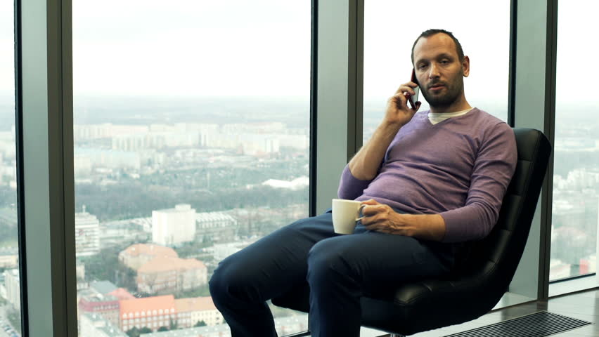 Man talking on cellphone and drinking coffee on chair by window at home  | Shutterstock HD Video #20819893