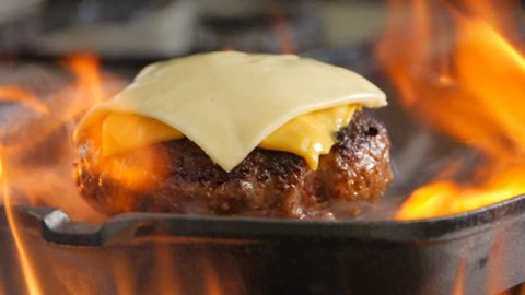 Homemade burger with cheese on a grill pan, slow motion