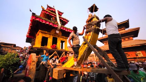 BHAKTAPUR, NEPAL - APRIL 9, 2016: Preparation for Nepalese New Year (Bisket Jatra) celebration. Two men tie the deity to the big deity waggon. Many people wait for spectacle