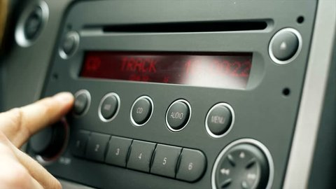 Driver playing car radio, stations shifting