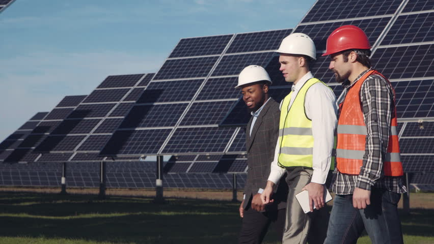Three mixed ethnic men in uniform and hard hat walking around solar power station and examining it. Side view   Shutterstock HD Video #20858245