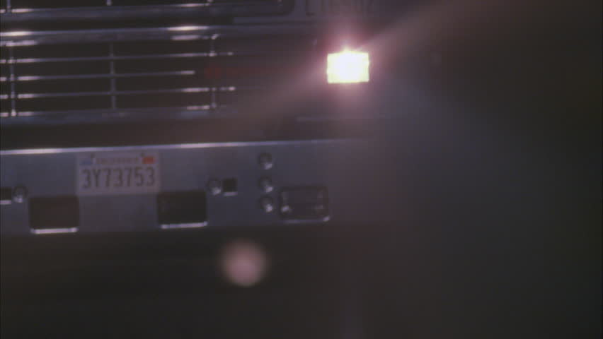 night MPOV ing front grill headlight semi truck approx. 18 seconds , then light green classic muscle car Trans AM pulls up along side semi, car swerves back forth truck Car speeds away, semi