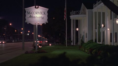 night raked right, from lit sign McCormick Mortuary funeral home elegant yellow colonial style wood building with pillars, American Flag