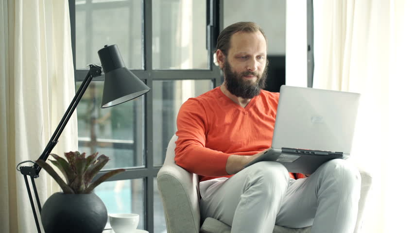 Young man using laptop sitting on armchair at home  | Shutterstock HD Video #20908531