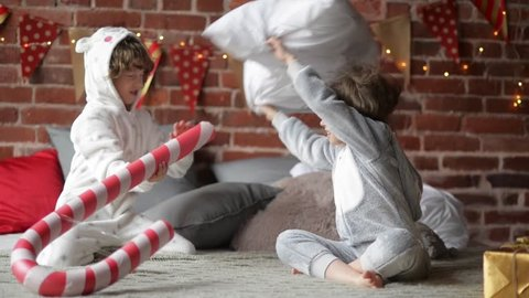 Playful siblings in warm xmas pajamas fighting with pillows at home, brother and sister playing together on Christmas morning, merry christmas