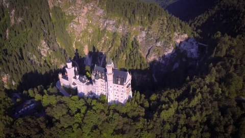 Aerial rotating motion Neuschwanstein castle disneyland inspiration romantic fairytale fantasy mountain forest landscape sunny day Germany
