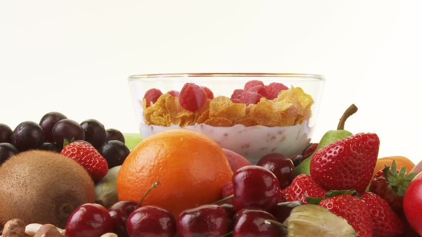 Fresh fruit and bowl of cornflakes, milk and berries
