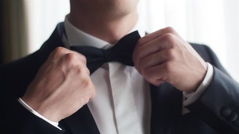 Man straightens bow-tie close up slow motion. Well-dressed young man puts and adjusts classic black bowtie on white shirt no face only torso. Success style confidence establishment luxury life concept