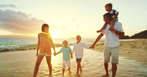 Happy family walking down the beach at sunset