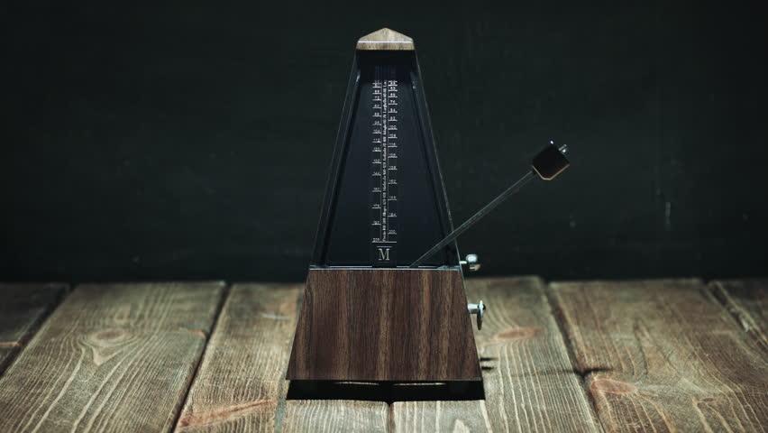 Vintage metronome with golden pendulum beats slow rhythm on the dark background