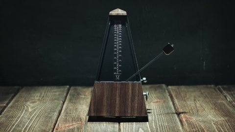 Vintage metronome with golden pendulum beats slow rhythm on the dark background