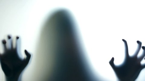 Crooked hands of evil female silhouette scratching glass, psycho on the loose. Scary ghostly creature behind the glass
