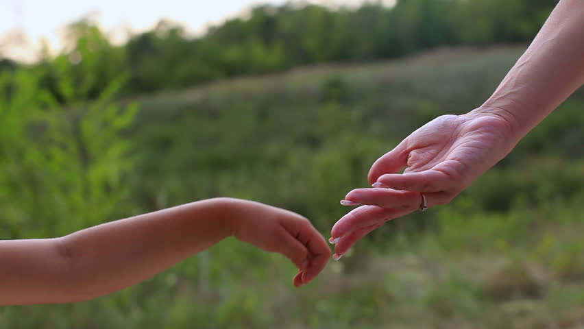 Mother and daughter hands on green background. Hand in hand. Concern for children