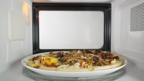 Man reheating baked seafood pizza in the microwave oven. He opens the door of the oven and takes out a dish with hot pizza Frutti di Mare topped with mussels shrimp and olives.