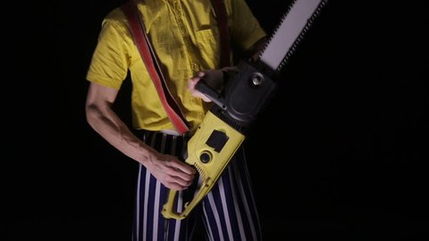 Scary clown with a chainsaw in the dark. Clown murderer threatening you.