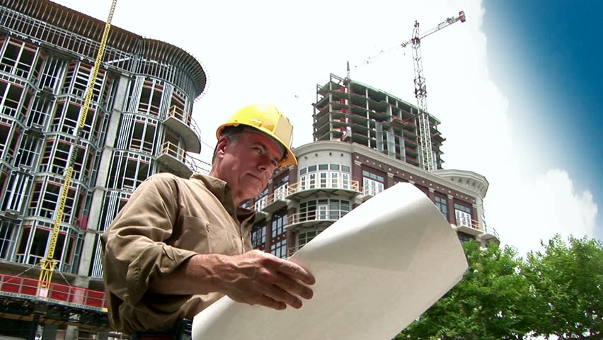 architect looking at building plans, then rolling them up and smiling at the camera.