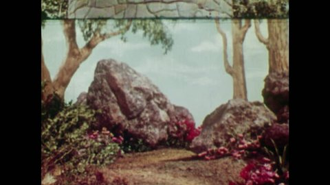 ANIMATED 1950s: Witch walks towards Rapunzel's tower. Young man sees a witch coming so hides behind a rock. Witch calls up to Rapunzel in her tower as young man watches.