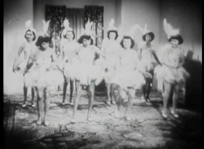 Women in costume rehearsing dance routine in living room
