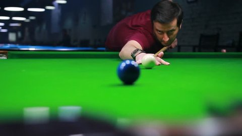 Close up footage above a hole and a snooker player hitting the blue ball and makes a point...
