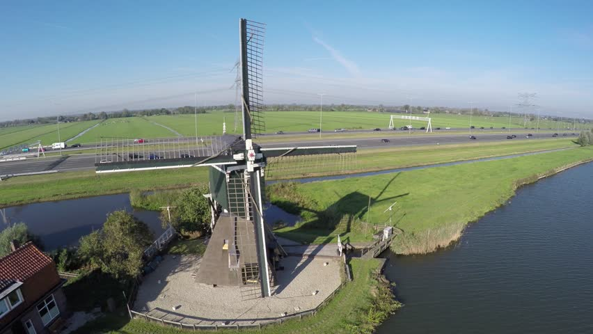 Aerial flying over typical Dutch landscape moving near windmill moving from left to right past canal in polder old Dutch windmill located near water and behind mill modern highway with traffic 4k