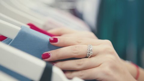 Close-up of female hands plucked a hanger with clothes. Beautiful female hands with neat manicure. Female manicure: the red gel-polish. Nail polish