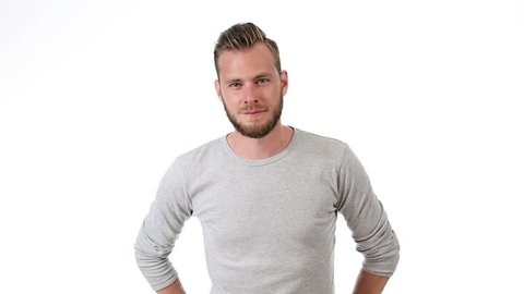 Smiling man wearing a grey shirt with rolled up sleeves, standing in front of a white background.