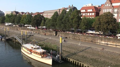 Bremen, Germany, 11 Sep. 2016, River Elbe with gastronomy restaurants, ships, people, bridge and skyline at location Schlachte / River Elbe panning with docks and skyline Bremen location Schlachte
