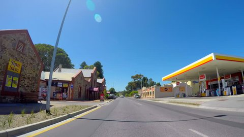 MCLAREN VALE, SOUTH AUSTRALIA - NOVEMBER 5, 2016: Automobile POV driving through the main township of McLaren Vale along Main Road, sunny with lens flare, fast motion timelapse.