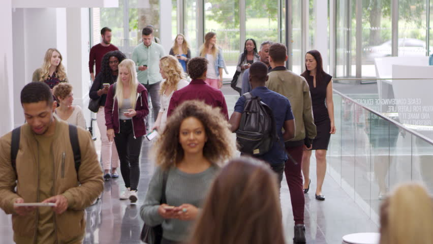 Students and teachers walk in foyer of a modern university, shot on R3D