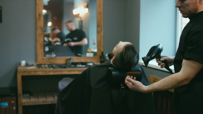 4K CINEMAGRAPH - Young handsome bearded Caucasian man getting a his hair blow dried in a modern barber shop. Seamless loop. 4K UHD Raw edited footage