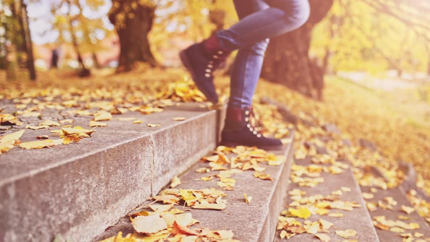 Unrecognizable Woman Feet walking Down the Stairs covered with Leaves in Autumn Park. 4K DOLLY SHOT, Close up on shoes. Girl enjoying cool fall weather outdoors, wearing stylish fall boots. #21257242