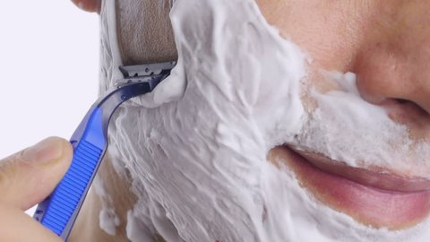 Man shaving with foam and manual razer. Close up of man shaving beard.