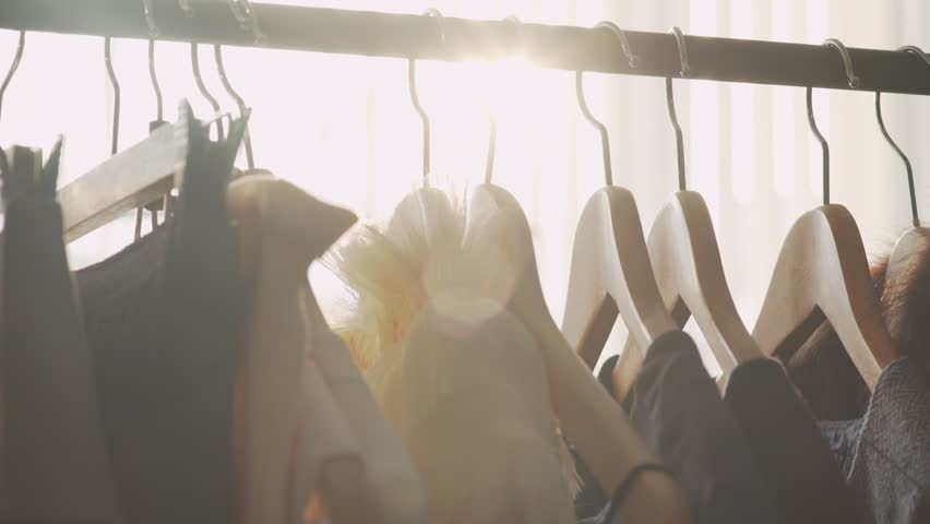 Close-up: a hanger for clothing. Clothes hangers. Designer clothing collection. Designer with a ready collection. Atelier, bathed in natural sunlight.