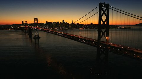 Aerial sunset view of the Oakland Bay Bridge at night with the illuminated light from traffic, San Francisco, North America