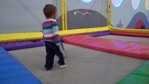 4K Child runs around trampoline, stumbles and falls down, trekking shot