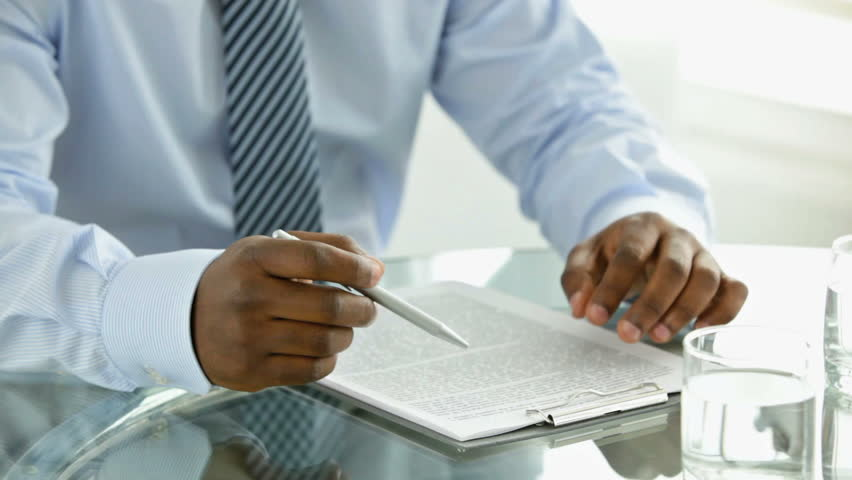 An Afro-American businessman looking through a document attached to a clipboard